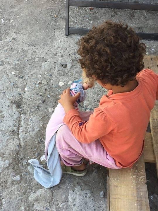 Una nena jugant amb una nina en un dels camps de refugiats a Grècia