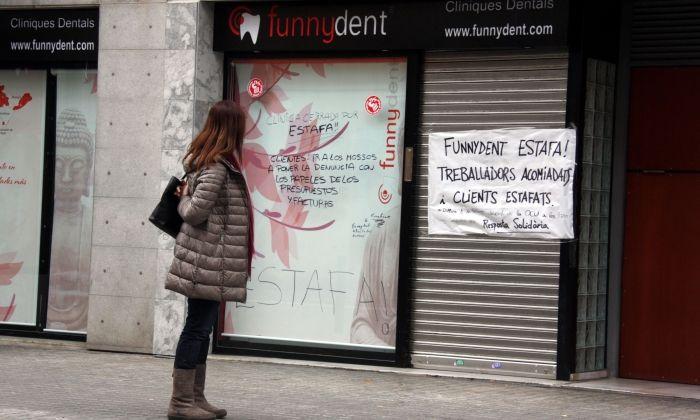 Una noia mira les pancartes de protesta a l'aparador de la clínica dental Funnydent, a Mataró. Foto: ACN