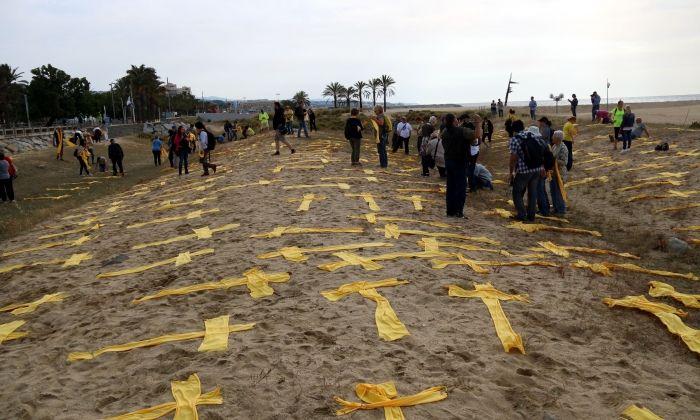 Tovalloles grogues amb forma de creu a la platja de Mataró. Foto: ACN