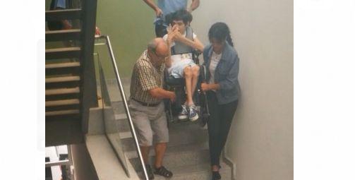 Trasllat d'un infant en cadira de rodes per l'escala. Foto: cedida